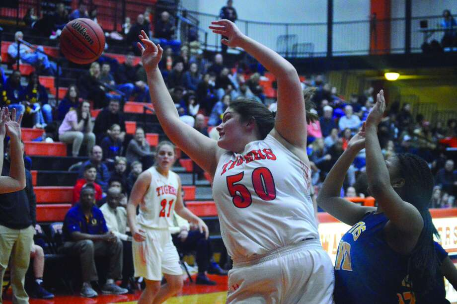 Edwardsville senior forward Sydney Kolnsberg reaches for a rebound during the first quarter of Tuesday's Southwestern Conference home game against the Panthers.