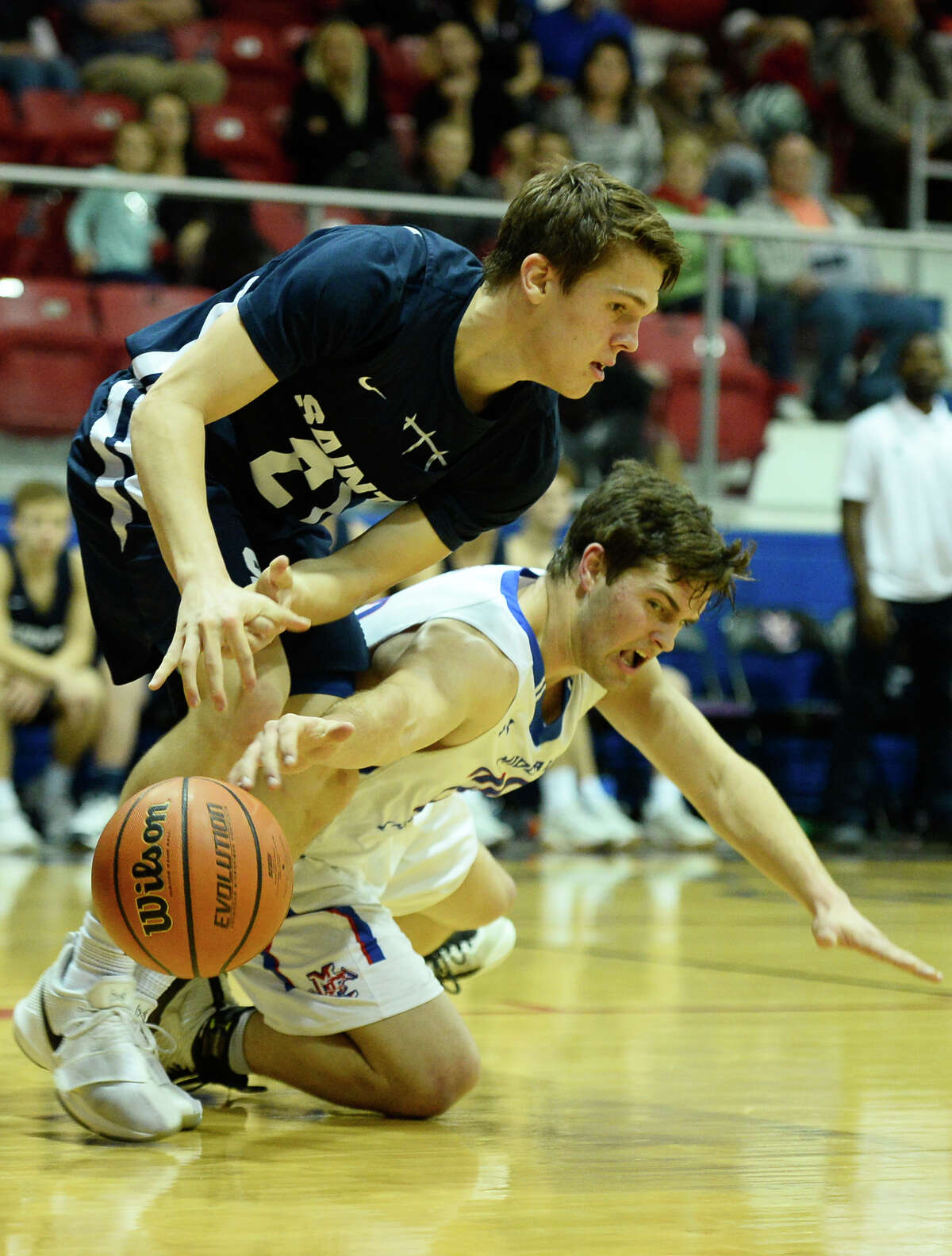 Midland Christian's Silas Crews (20) goes after the ball against Fort Worth All Saints Matt Albritton (21) on Feb. 6, 2018, at McGraw Events Center. James Durbin/Reporter-Telegram