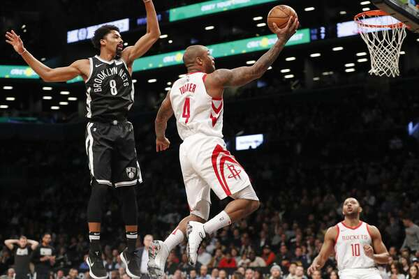 Houston Rockets forward PJ Tucker (4) goes airborne in front of Brooklyn Nets guard Spencer Dinwiddie (8) during the first half of an NBA basketball game, Tuesday, Feb. 6, 2018, in New York. Houston Rockets guard Eric Gordon (10) watches from the floor. (AP Photo/Kathy Willens)