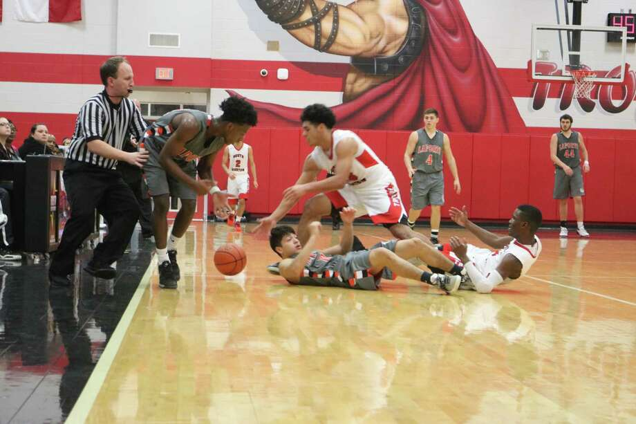 A loose ball in the fourth period has both South Houston and La Porte players on the floor, while a referee attempts to stay on top of the play. Photo: Robert Avery