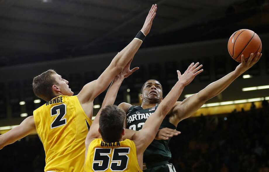 Michigan State guard Miles Bridges, right, drives to the basket as Iowa's Jack Nunge (2) and Luka Garza defend during the second half in Iowa City, Iowa. Bridges scored 25 points as Michigan State won 96-93. Photo: Charlie Neibergall, Associated Press