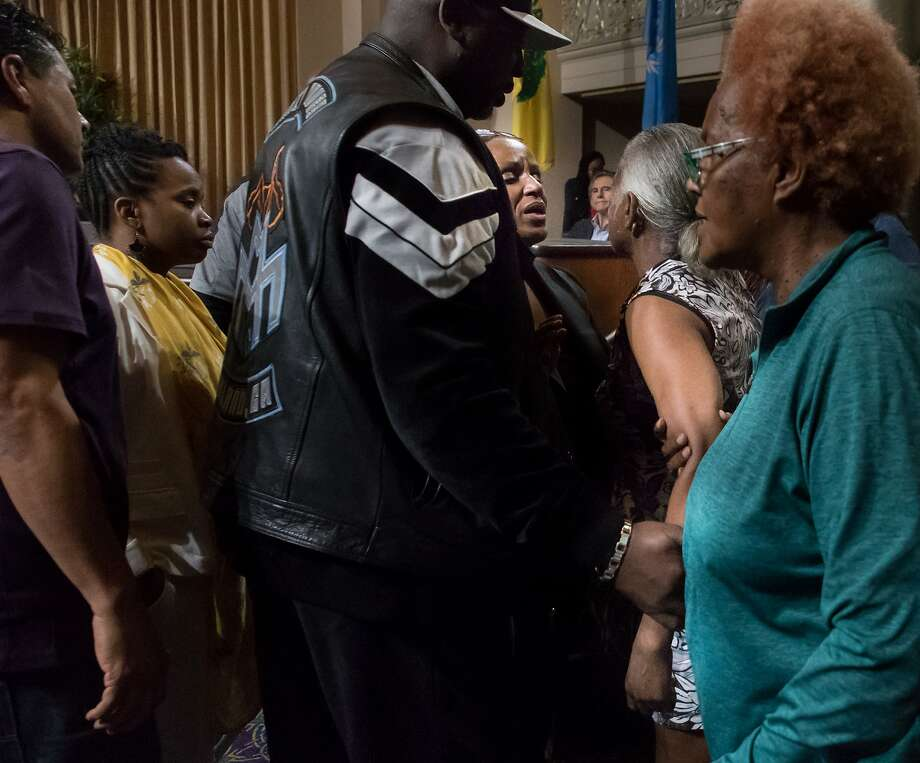 Councilwoman Desley Brooks steps down from her seat to calm Etta Johnson who was supporting her during Tuesday's Oakland City Council meeting. Photo: Paul Kuroda, Special To The Chronicle