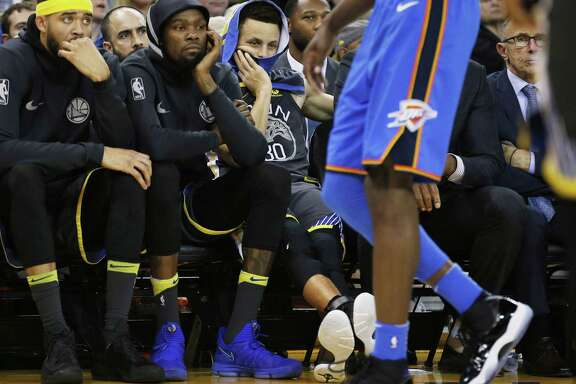 JaVale McGee, Kevin Durant and Stephen Curry struggle to watch the end of the Warriors' loss at Oracle Arena Tuesday.