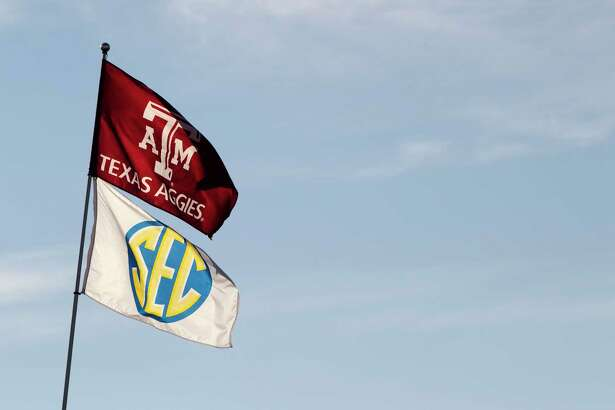 Texas A&M and Southeastern Conference flags fly over the tailgating area before an NCAA college football game between Texas and Texas A&M at Kyle Field Thursday, Nov. 24, 2011, in College Station.