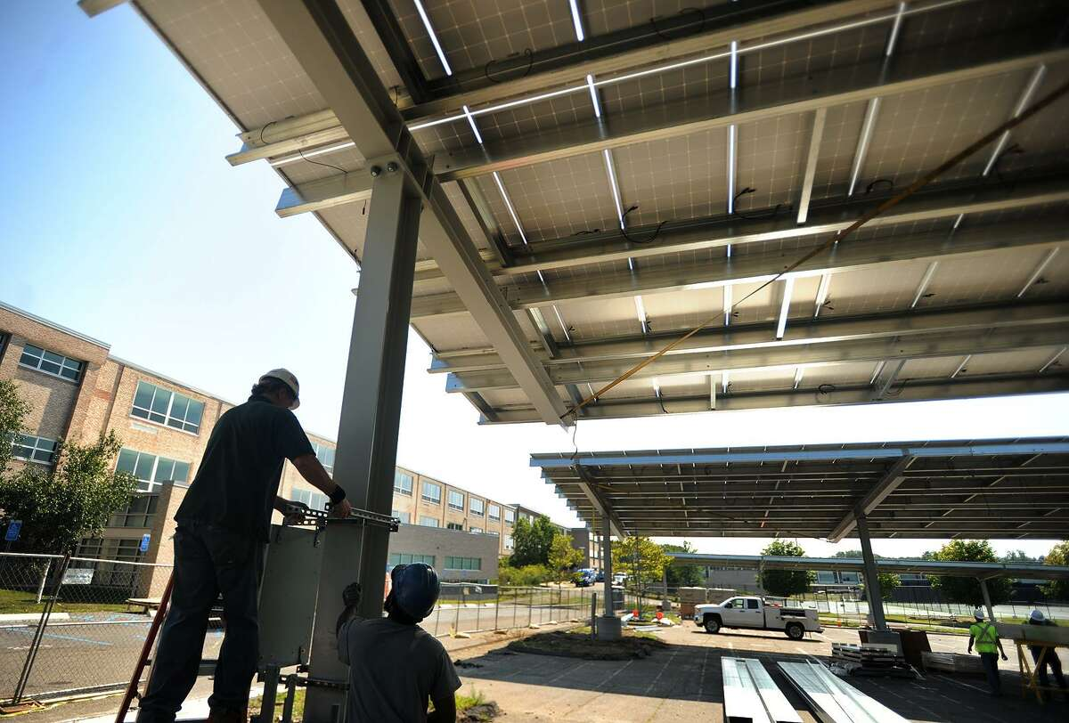 Workers install massive solar arrays in August 2017 at Fairfield Ludlowe High School in Fairfield, Conn. The state's solar industries employment stayed flat in 2017 at nearly 2,200 people, according to the Washington, D.C.-based Solar Foundation.