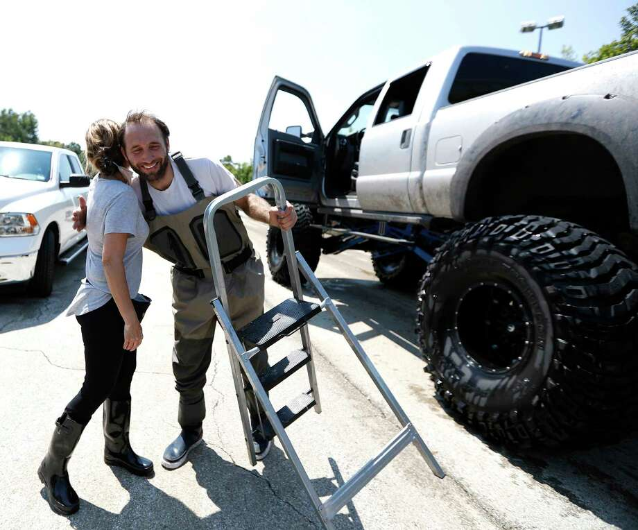 Chris Ginter gets a hug from Nancy Nejad, after Ginter helped her and her husband, Sonny, get them back to dry land from their home in the Memorial Thicket subdivision, Saturday, Sept. 9, 2017. Ginter has become a hero, driving around in his brother's monster truck, first saving people from rising floodwaters, and now helping people get back in to roads that are impassable by trucks in the Memorial area, east of Highway 6, off of Memorial Drive, in Houston.  ( Karen Warren / Houston Chronicle ) Photo: Karen Warren, Staff / @ 2017 Houston Chronicle