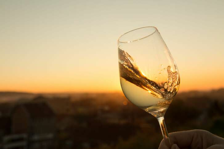 White wine in crystal glass against sunset.