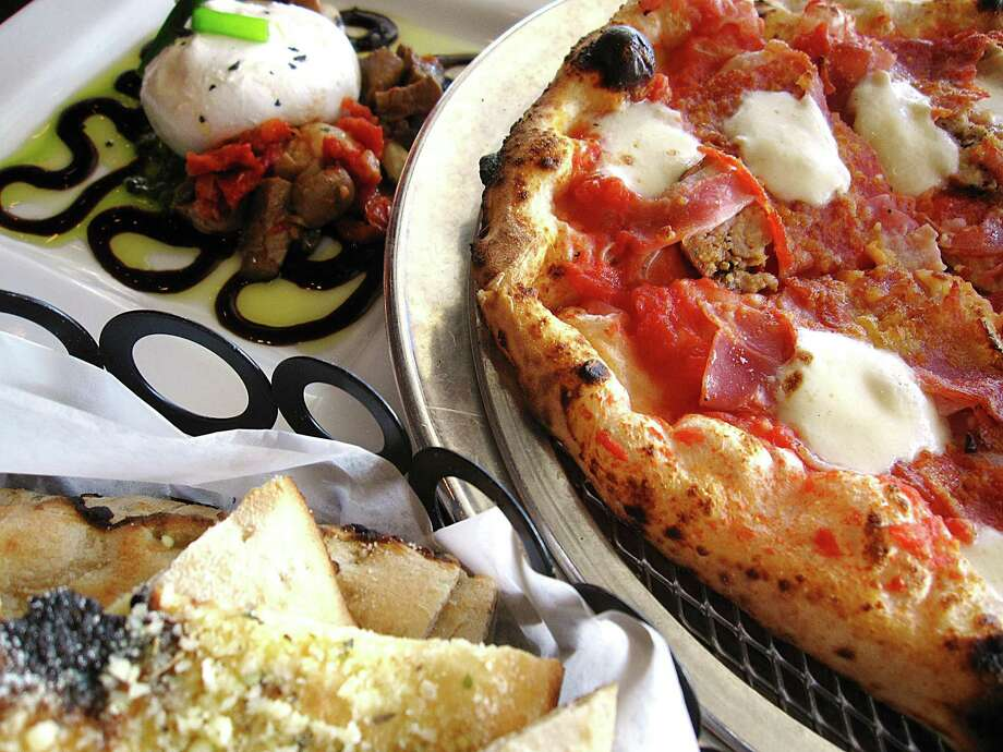 Burrata with marinated mushrooms and sun-dried tomatoes, left, and a Pork Love pizza with sausage, speck, soppressata, pancetta and housemade mozzerella at Dough Pizzeria Napoletana on Blanco Road. Photo: Mike Sutter /San Antonio Express-News