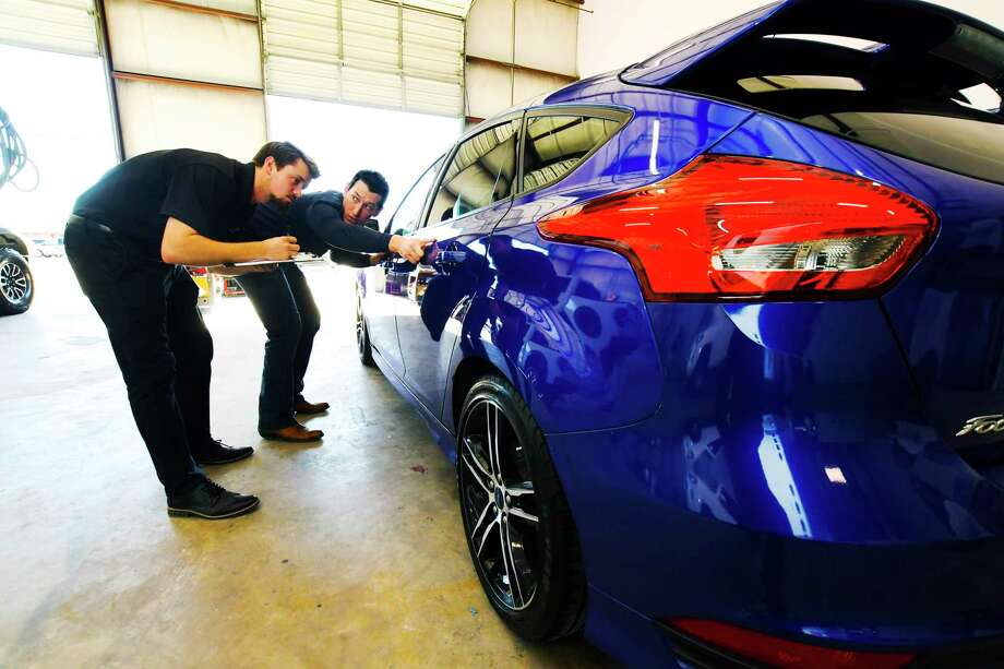 Kevin Taylor, owner of the Maaco Collison Repair & Auto Painting shop off FM 1960 in the Cy-Fair area, is one of the youngest Maaco shop owners in the country. Employee Taylor Hanzelka, and Taylor inspect a vehicle for body work. Photo: Tony Gaines, Photographer