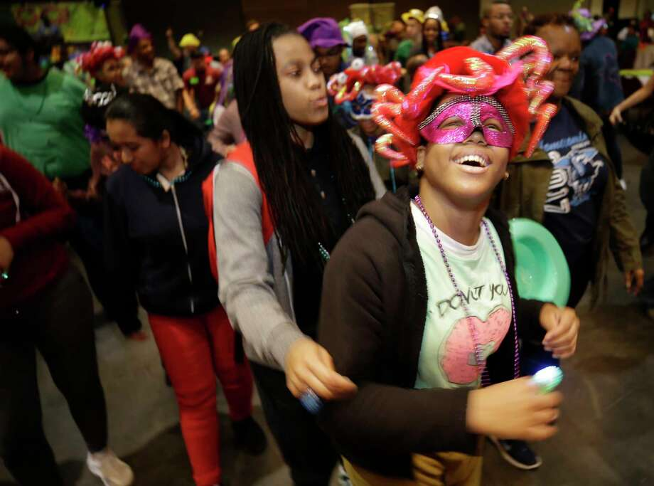 Alicia McDaniel, center, a life skills teacher with Sterling High School, dances with 9th grader, Jayden Wiggins, right, during the annually Mardi Gras Ball for Special People held at Moody Gardens Convention Center Sunday, Jan. 28, 2018, in Galveston. The free event provides food, fun and entertainment for people with special needs and their immediate families. ( Melissa Phillip / Houston Chronicle ) Photo: Melissa Phillip, Houston Chronicle / © 2018 Houston Chronicle