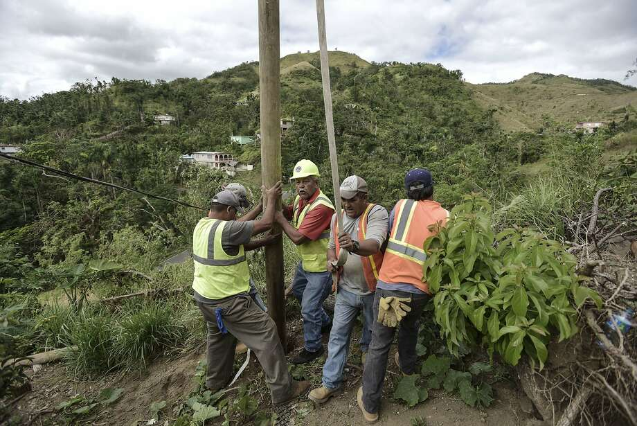 Residents of Coamo install a power pole in an effort to return electricity to the southern mountain town four months after Category 4 Hurricane Maria. Photo: Carlos Giusti, Associated Press