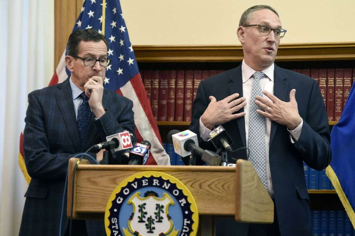 Gov. Dannel P. Malloy, left, listens as Ben Barnes, Secretary of the State of Connecticut Office of Policy and Management, right, speaks about the budget adjustments they are proposing for the 2019 Fiscal Year during a press conference at the state Capitol on Monday.