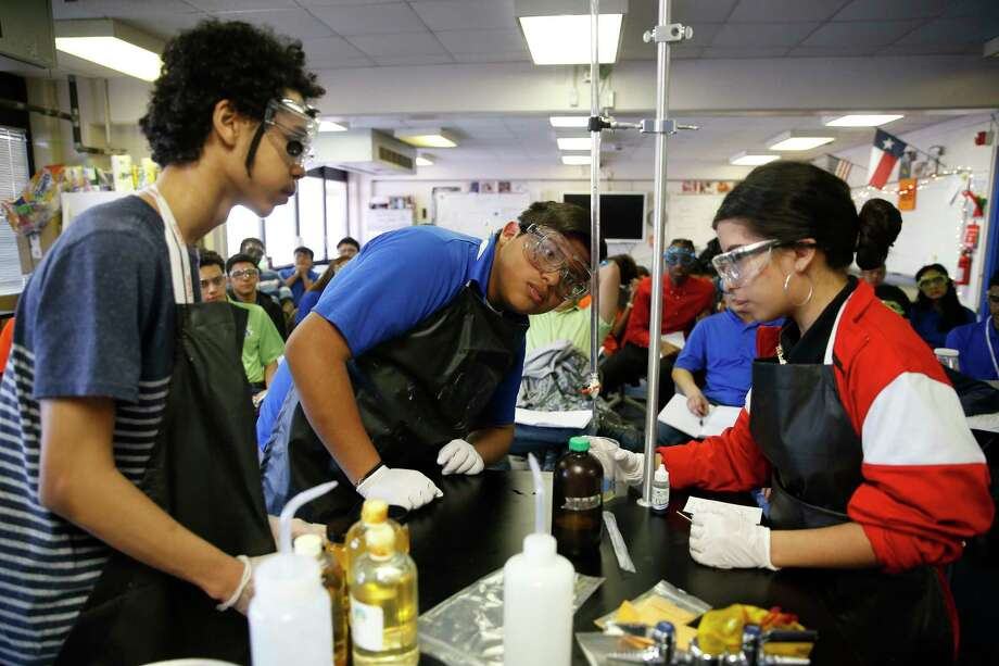 Junior Valentin Roman, center, performs a titration with classmates as they help with an experiment during a presentation on biodiesel during a joint environmental science and bio-tech engineering class at the Energy Institute High School, a STEM-focused magnet school in Houston ISD, Tuesday, Jan. 30, 2018 in Houston. ( Michael Ciaglo / Houston Chronicle) Photo: Michael Ciaglo, Houston Chronicle / Michael Ciaglo