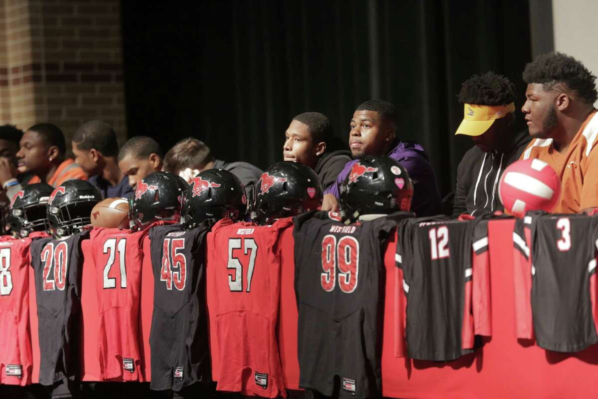 Members of Westfield High School's football team sits on the school's stage during signing day at Westfiled High School on Wednesday, Feb. 7, 2018, in Houston.