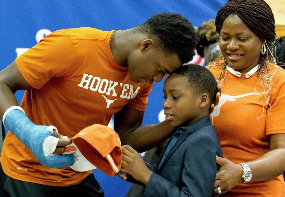 Oak Ridge defensive end Joseph Ossai, left, shares a moment with his younger brother Chidera beside their mother Emmanuela after signing to play football for University of Texas during a National Signing Day ceremony at Oak Ridge High School, Wednesday, Feb. 7, 2018. Photo: Jason Fochtman, Houston Chronicle / © 2018 Houston Chronicle