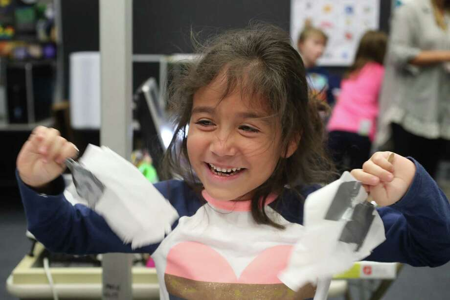 Ed White E-STEM Elementary first-grader Aliana Newswander cools herself with the windmill blades she designed Wednesday, Jan. 24, 2018, in El Lago. STEM education is an immersive experience from the classroom to the lab to the library for students at Clear Creek ISD Ed White Elementary in El Lago. In the engineering lab, the first graders are building and testing windmills while the fifth graders are building a dam to watch a water release, potential innovation to advise those who run water basins and gates that could cause or prevent flooding like in Hurricane Harvey. ( Steve Gonzales / Houston Chronicle ) Photo: Steve Gonzales, Houston Chronicle / © 2018 Houston Chronicle