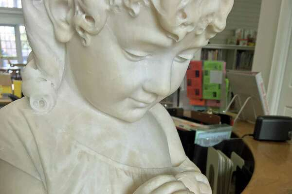 The bust of a small child graces a counter in the children's department at the Perrot Memorial Library in Greenwich. Artist Jeffrey Damberg, of Greenwich, helped to restore the pinkie finger on the right hand of the statue, one of several sculpture restorations in which he has been involved.