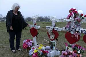 Wearing her mom's sweater, Michelle Shields touches the memorial cross for her mother, Lula Woicinski White.