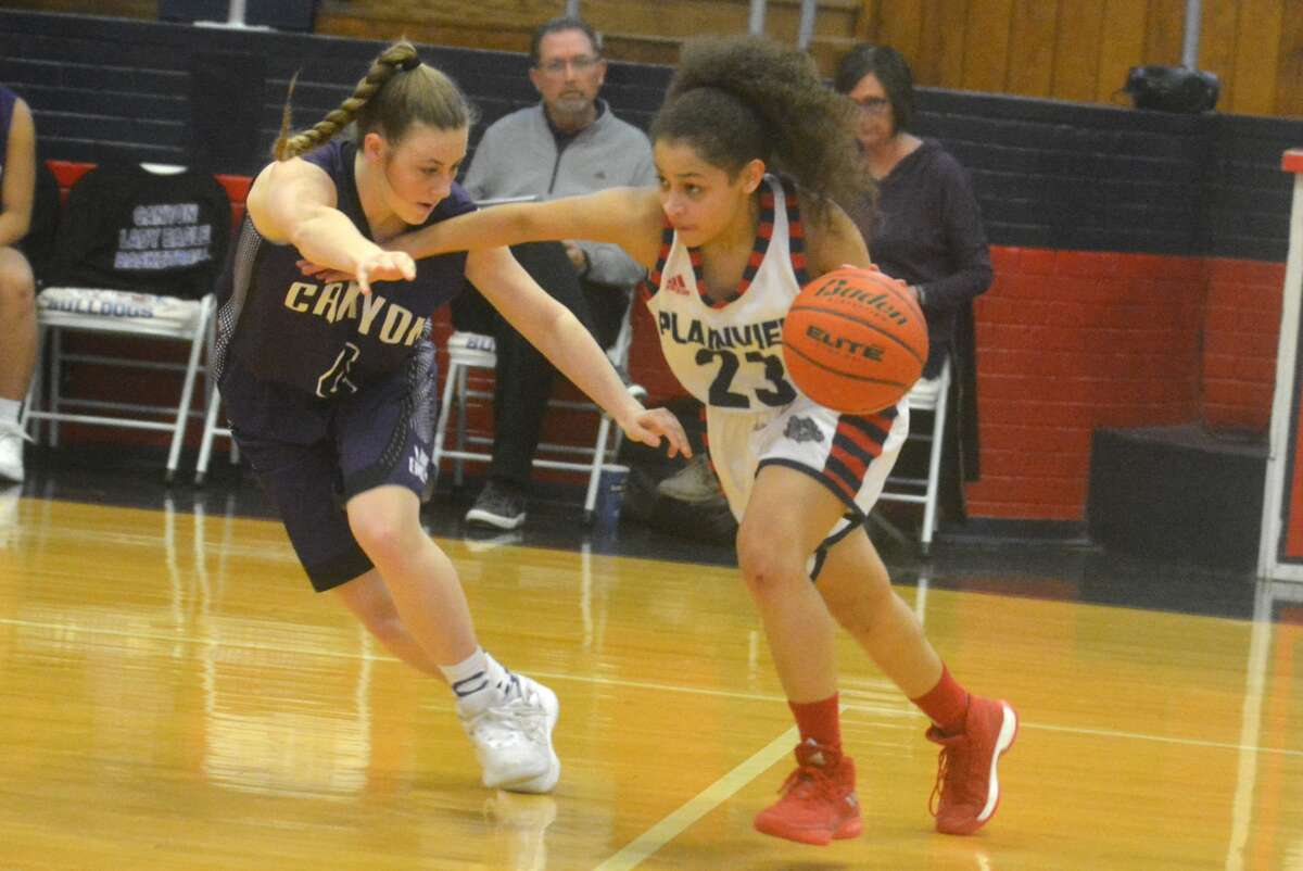 Plainview's Osen Ellis, 23, tries to dribble past a Canyon defender during a District 3-5A girls' basketball game at the Plainview High School gym Tuesday night. Plainview finiished their regular season in third place in the district and will advance to the postseason playoffs next week.