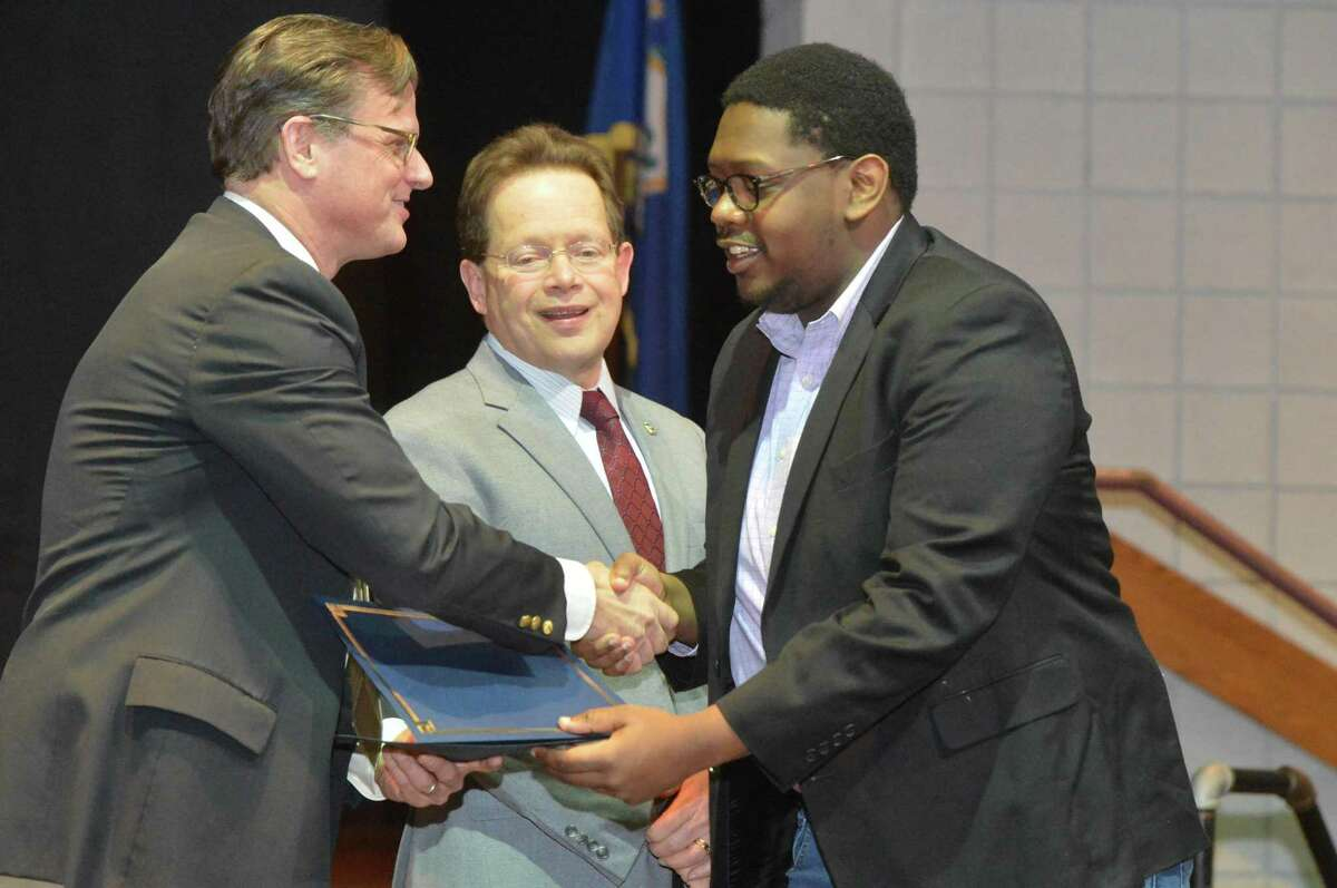 Doug Adams (left), senior director of GGP, presents a certificate to Noah Andrew Ruffin of Norwalk, right, after his completion of a retail customer service and sales program in partnership with Norwalk Community College. Construction continues in early 2018 on GGP's SoNo Collection mall with an anticipated opening date in late 2019.