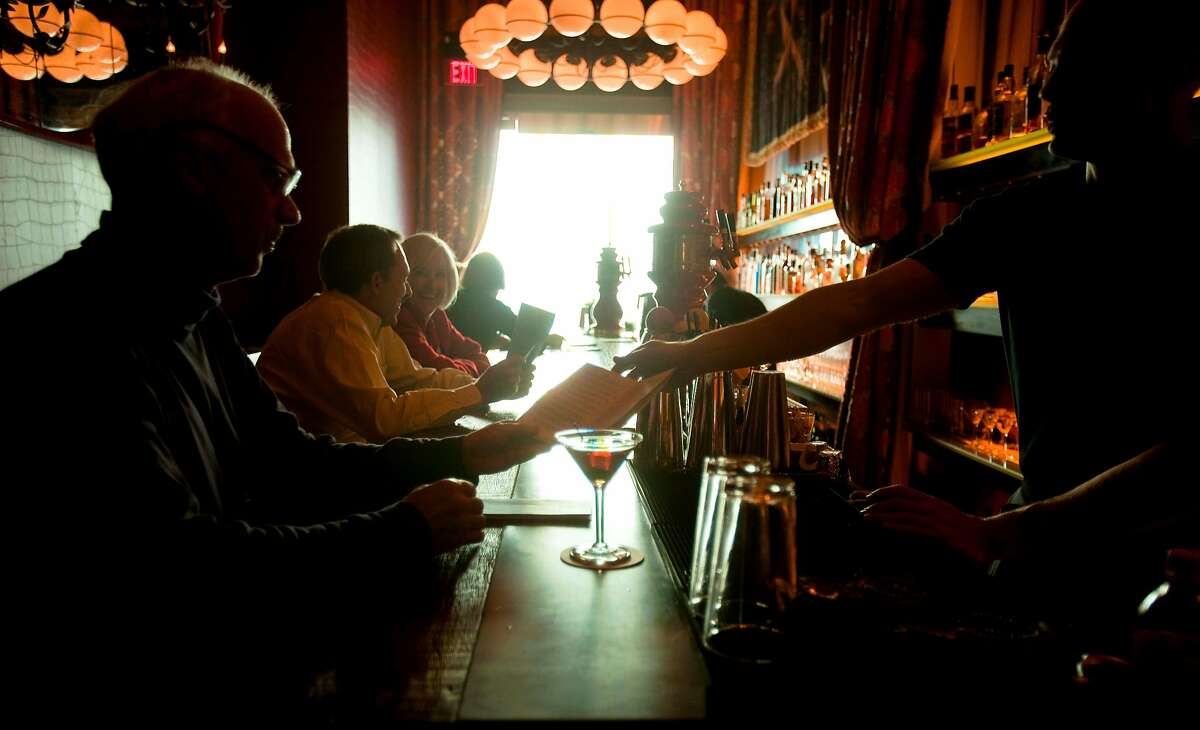 Bartender Seth Laufman, right, passes a drinks menu after serving a Rob Roy cocktail, center, to first-time customer Tom Bostock, of San Francisco, at the bar area in Gitane Restaurant & Bar in San Francisco, Calif. on Tuesday, July 21, 2009.