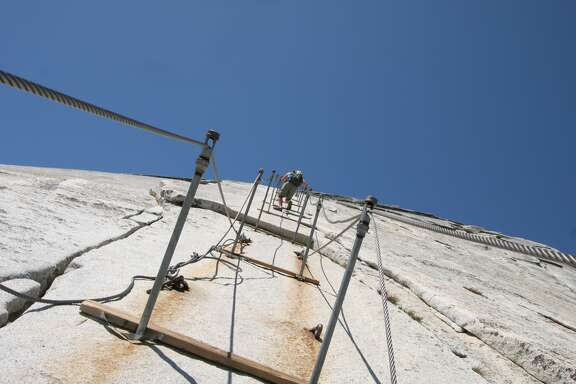Hiker nearing the peak of Half Dome. Cables are clearly visible, as well as sheer cliff (from a near vertical perspective).