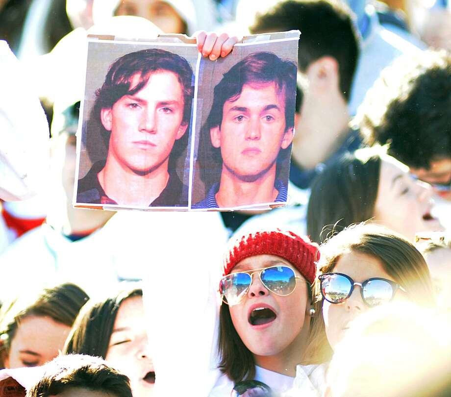 A person in the New Canaan High School student body cheering section holds up New Canaan Police Department mugshots of Darien High School football players Brian Minicus, left, and teammate Jack Joyce, both 18, during the 2017 Turkey Bowl high school football game between Darien High School and New Canaan High School at Boyle Stadium in Stamford on Nov. 23. New Canaan won the game 27-0, beating an undefeated Darien team that was without starting quarterback Joyce and star defensive back Minicus, both of whom accepted accelerated rehabilitation terms, which will drop assault charges in exchange for community service. Photo: Bob Luckey Jr. / Hearst Connecticut Media / Greenwich Time