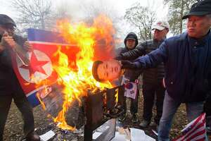 "Likenesses of North Korean Leader Kim Jong-un and a North Korean flag are burned during a demonstration by Korean Americans at Haden Park, Wednesday, Feb. 7, 2018, in Houston. ""We are protesting the North Korean regime and the threat they post to the Korean Peninsula and the United States,"" said Mark Shim with the Korean American Association of Houston."
