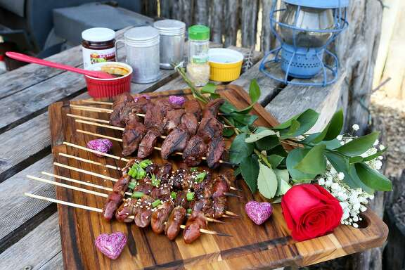 Skewers of chicken heart yakitori (front) and beef hearts made into anticuchos, prepared on the grill using Asian and South American methods, respectively.