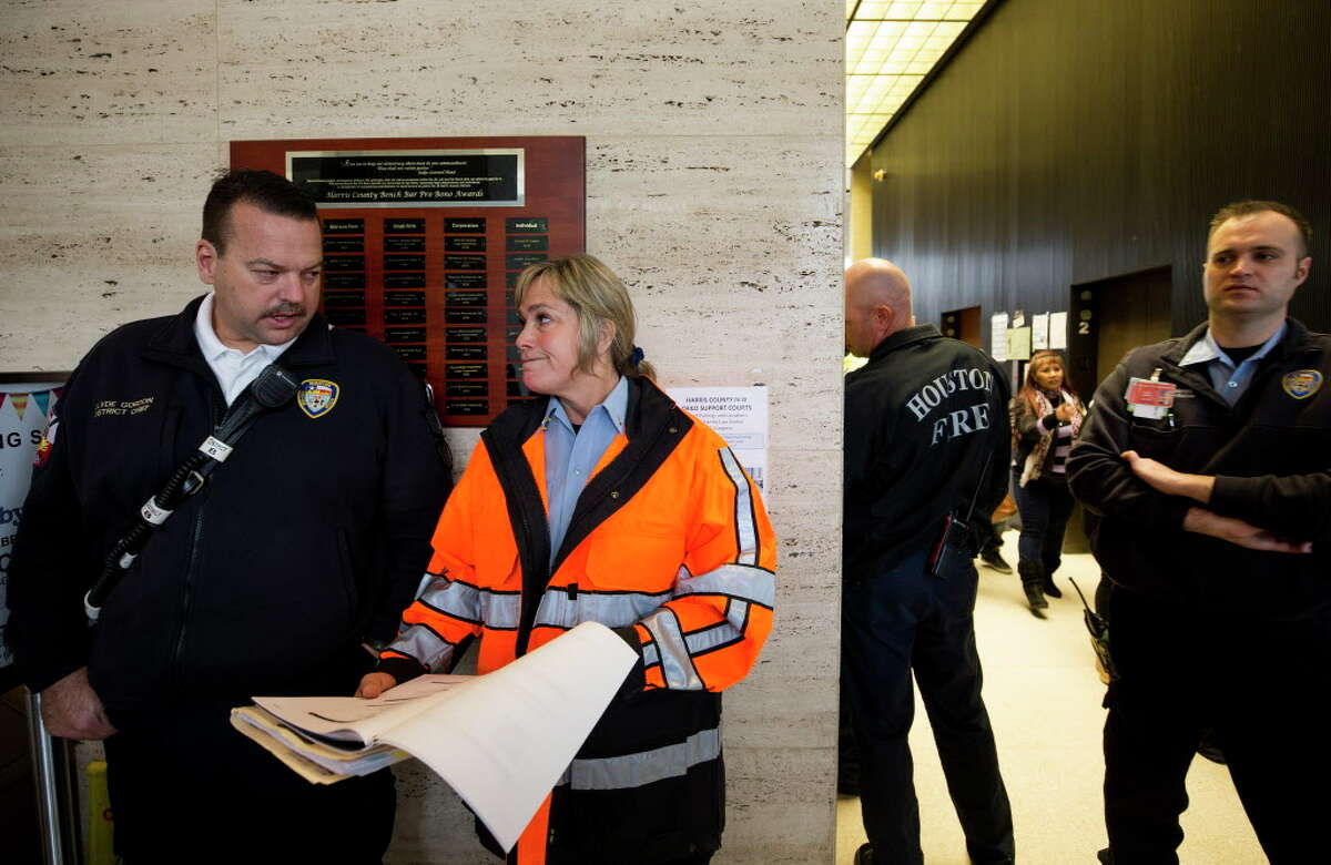Houston Fire Department district chief Clyde Gordon, left, and fire marshall Lisa Kimball, center, talk after an inspection of the Family Law Center building Wednesday, Feb. 7, 2018, in Houston. The building, lacking sprinklers, was slated for destruction, but due to Hurricane Harvey now houses all 16 misdemeanor courts.