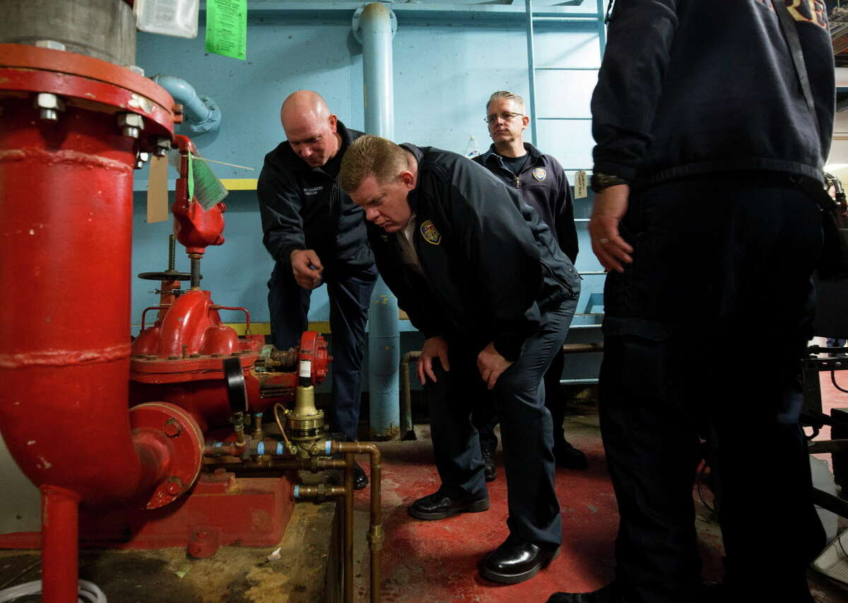 Houston Fire Department district chief Justin Barnes, center, inspects a water pump located in the basement of the Family Law Center building Wednesday, Feb. 7, 2018, in Houston. The building, lacking sprinklers, was slated for destruction, but due to Hurricane Harvey now houses all 16 misdemeanor courts.