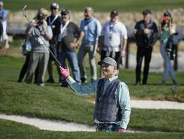 Bill Murray tosses his club after hitting out of a bunker on the 17th hole during the celebrity challenge event of the AT&T Pebble Beach National Pro-Am golf tournament Wednesday, Feb. 7, 2018, in Pebble Beach, Calif. (AP Photo/Eric Risberg)
