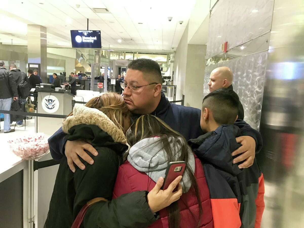 Jorge Garcia hugs his wife, Cindy Garcia, and their two children on Jan. 15 at Detroit Metro Airport moments before boarding a flight to Mexico. Garcia, who had lived in the United States for nearly 30 years, was deported to Mexico. (Niraj Warikoo /Detroit Free Press via AP)