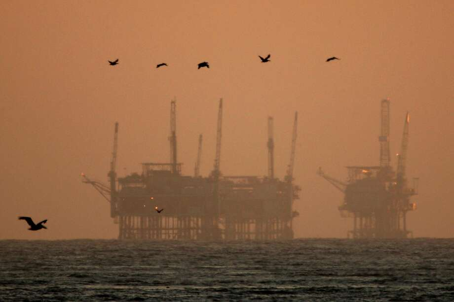 California brown pelicans fly near offshore oil rigs after sunset on July 21, 2009 near Santa Barbara, California. Photo: David McNew, Getty Images