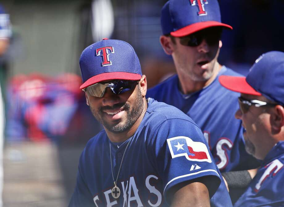 FILE - This March 28, 2015 file photo shows Seattle Seahawks quarterback Russell Wilson talking with fellow Texas Rangers in the dugout during a spring training baseball game between the Texas Rangers and the San Diego Padres in Surprise, Ariz. Wilson has been traded from the Texas Rangers to the New York Yankees. The Rangers selected Wilson in the Triple-A portion of the Rule 5 draft during the winter meetings in December 2013, about two months before he led the Seahawks to a win over Denver in the Super Bowl. (AP Photo/Lenny Ignelzi) Photo: Lenny Ignelzi, Associated Press