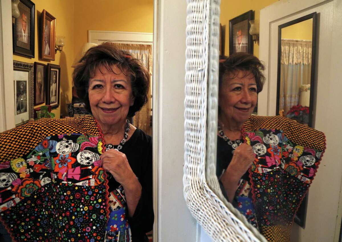Diana Sanchez Sanches shows a table runner that she pieced together and quilted and adorned with beads and buttons.