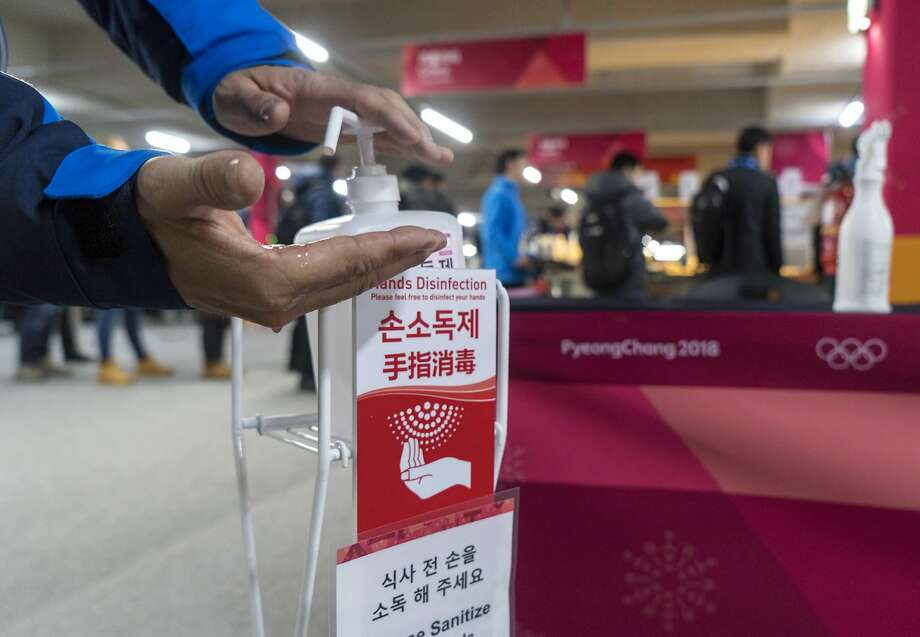A man sanitizes his hands at the entrance to the media cafeteria in Gangneung, South Korea, Wednesday, Feb. 7, 2018. South Korean authorities deployed 900 military personnel at the Pyeongchang Olympics on Tuesday after the security force was depleted by an outbreak of norovirus. (Paul Chiasson/The Canadian Press via AP) Photo: Paul Chiasson, Associated Press