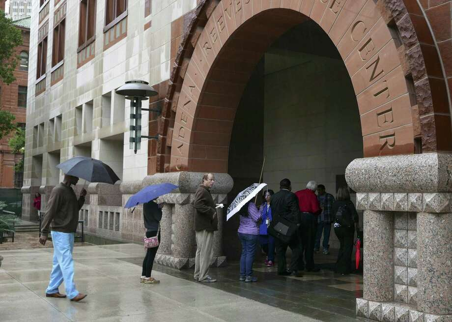 People wait to enter the Cadena-Reeves Justice Center in downtown San Antonio as rain falls in April 2015. The races to fill the benches in this building are often low profile but bear strict attention because of the important work that occurs in these courtrooms. Photo: Billy Calzada /San Antonio Express-News / San Antonio Express-News