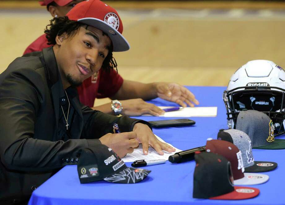 With his hat options lined out in front of him, Episcopal's Jaylen Waddle signs paperwork wearing his cap of choice (Alabama). Photo: Melissa Phillip, Houston Chronicle / © 2018 Houston Chronicle