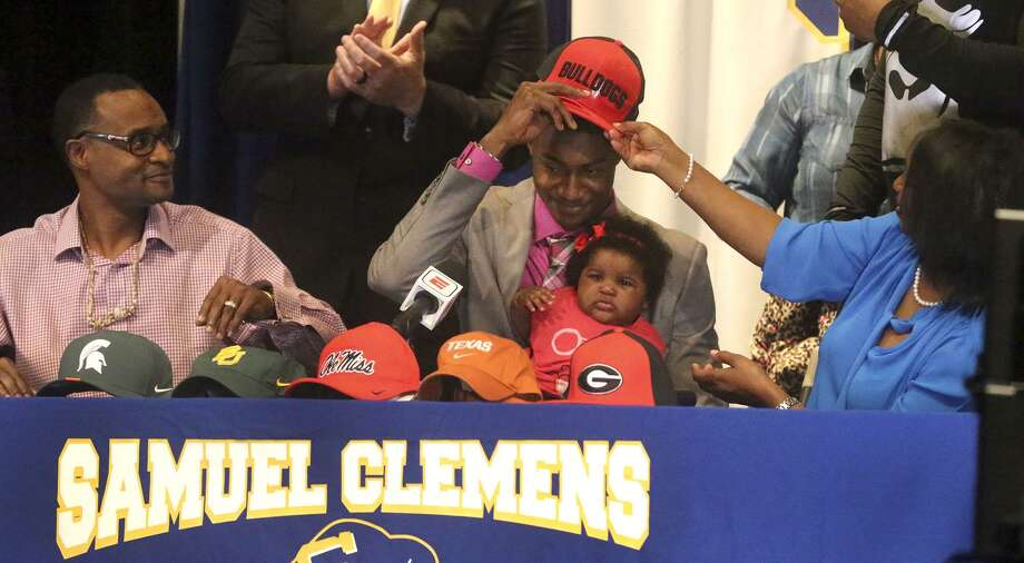 Clemens High School wide receiver Tommy Bush (center) tries on a Georgia Bulldogs hat during signing Wednesday February 7, 2018 at Clemens High School. In his lap is his niece Nayeli Bush-Mitchell, 6 months. On the left is his father Tommy Bush and on the right is hih mother Annie Bush. Photo: John Davenport, STAFF / San Antonio Express-News / ©John Davenport/San Antonio Express-News