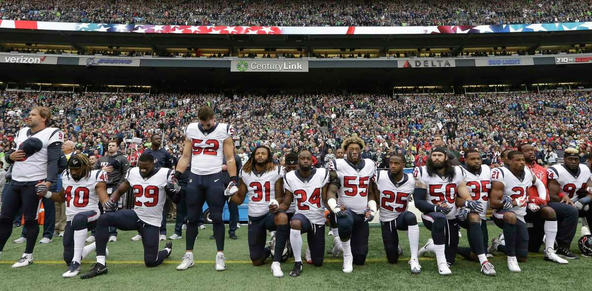 Houston Texans players kneel and stand during the singing of the national anthem before an NFL football game Oct. 29, 2017, in Seattle. (AP Photo/Elaine Thompson)