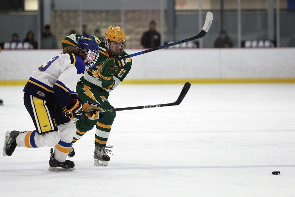 Midland's Travis Grimaldi (13) and Dow's Casey LaRue (13) rush to the puck during their game on Wednesday, Feb. 7, 2018 at Midland Civic Arena. (Samantha Madar/for the Daily News)