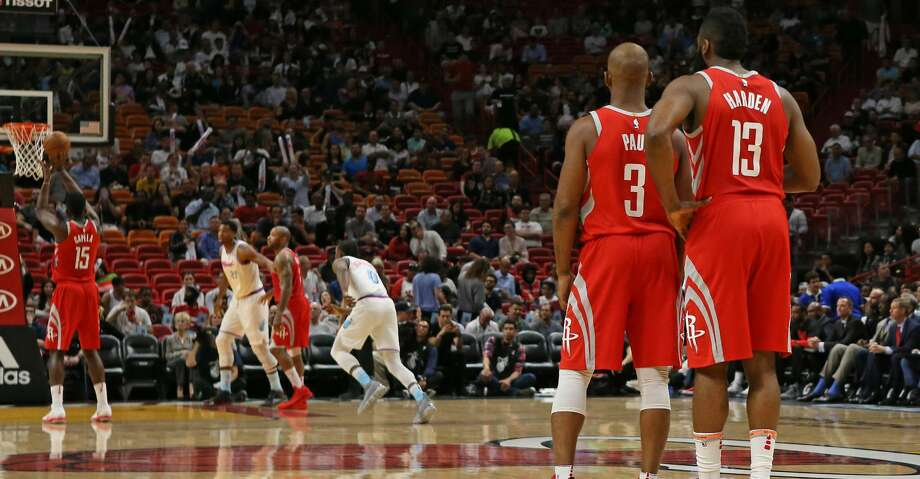 The Houston Rockets' Chris Paul (3) talks with teammate James Harden (13) as Clint Capela (15) shoots a free throw during the first quarter against the Miami Heat at the AmericanAirlines Arena in Miami on Wednesday, Feb. 7, 2018. (David Santiago/El Nuevo Herald/TNS) Photo: David Santiago/TNS