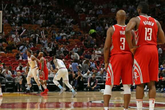The Houston Rockets' Chris Paul (3) talks with teammate James Harden (13) as Clint Capela (15) shoots a free throw during the first quarter against the Miami Heat at the AmericanAirlines Arena in Miami on Wednesday, Feb. 7, 2018. (David Santiago/El Nuevo Herald/TNS)