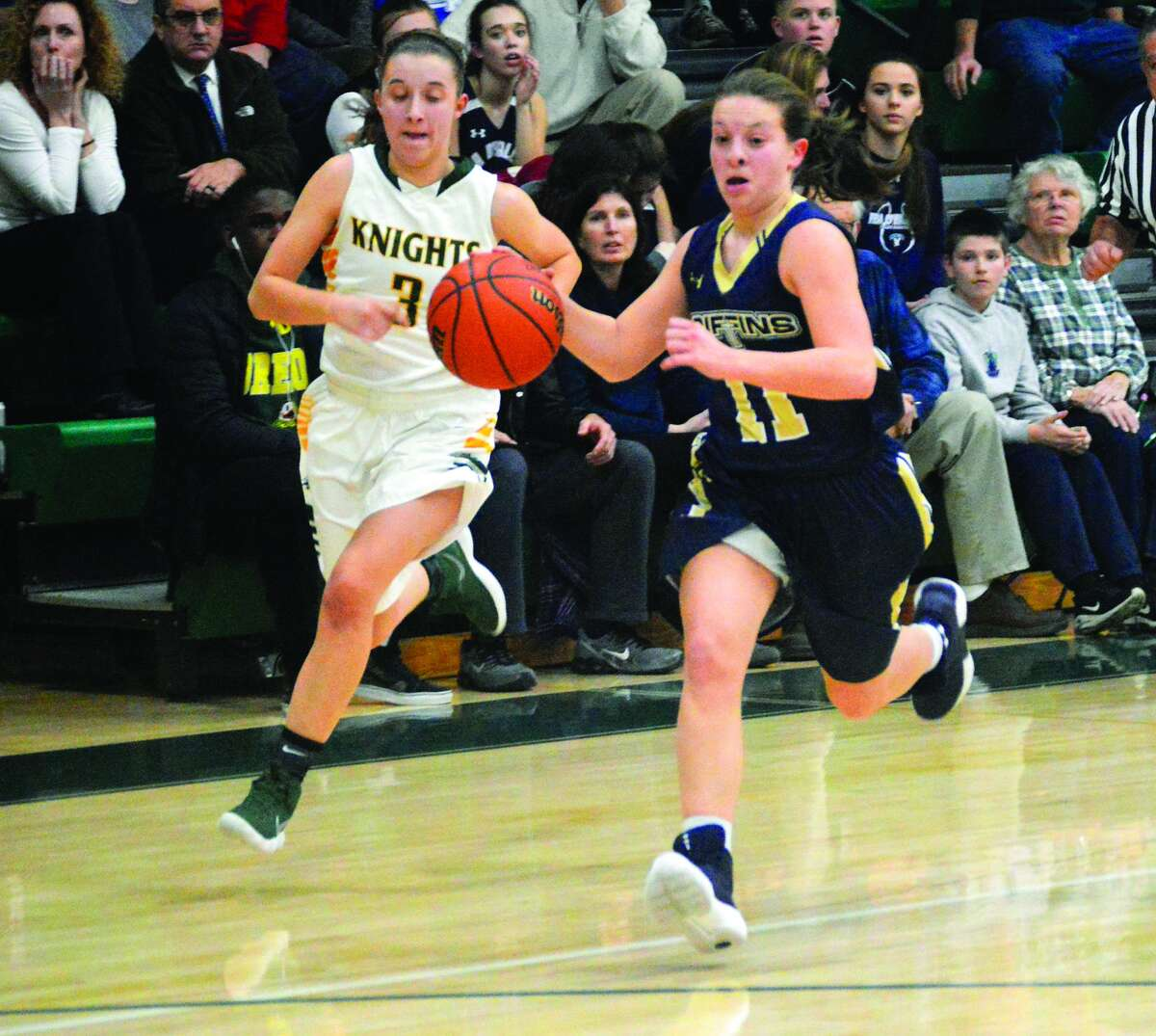 Father McGivney's Macy Hoppes, right, races the ball up the court with Metro-East Lutheran's Sami Kasting trying to chase her down.