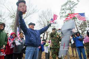 "Protesters hold U.S. and South Korean flags during a rally in Spring Branch on Wednesday. ""We are protesting the North Korean regime and the threat they pose to the Korean Peninsula and the United States,"" said Mark Shim of the Korean American Society of Houston."