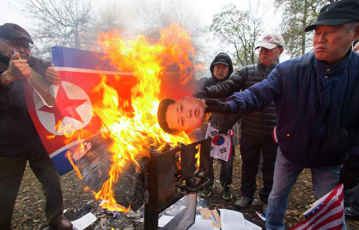 A North Korean flag and the likeness of North Korean leader Kim Jong Un are burned during a demonstration against an Olympic show of unity between the two acrimonious countries on Wednesday in Spring Branch.