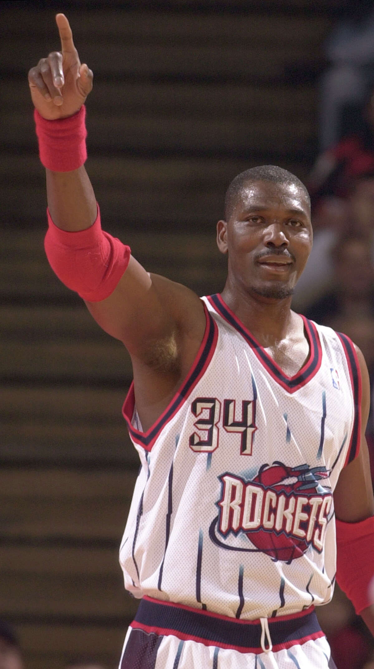 Hakeem Olajuwon celebrates after he started a fast break that ended in a Steve Francis slam during the first quarter of the Houston Rockets season finale vs. the Minnesota Timberwolves at Compaq Center in Houston, TX Tuesday night April 17, 2001. (Smiley N. Pool/Houston Chronicle) 04/17/01. HOUCHRON CAPTION (04/19/2001): A top priority for the Rockets during the off-season is setting the status of Hakeem Olajuwon, who hopes to play another season, with Houston as his preferred locale. HOUCHRON CAPTION (08/02/2001): Hakeem Olajuwon led the Rockets to two NBA championships. HOUCHRON CAPTION (08/04/2001): Houston has had many sports icons, and coincidentally, some of the best have worn the number 34: Earl Campbell (NOT PICTURED). Nolan Ryan (NOT PICTURED). Hakeem Olajuwon. In Sports 2, the Chronicle relives Olajuwon's stellar career and lists his 34 greatest moments as a Rocket. HOUCHRON CAPTION (08/05/2001): On the cover: Hakeem Olajuwon photographed by the Chronicle's Smiley N. Pool during his final game in a Rockets uniform on April 17, 2001. HOUSTON CHRONICLE SPECIAL SECTION: HAKEEM OLAJUWON: SPACE CITY DREAM.
