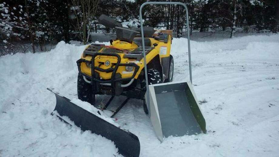 Above, the writer's snowblade-equipped ATV and 'Yooper Scooper' snow scoop have proven to be very dependable for tackling Michigan's unpredictable snowstorms. At right, when skies are gray and songbirds go into a feeding frenzy at birdfeeders, it is a good sign of an impending snowstorm. (Tom Lounsbury/Hearst Michigan)