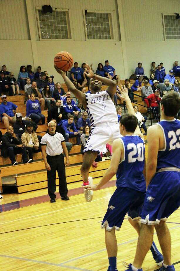 Dayton senior point guard Jerren Godfrey goes skyward to get over Barbers Hill defenders in the district rival game last Tuesday night. Photo: David Taylor